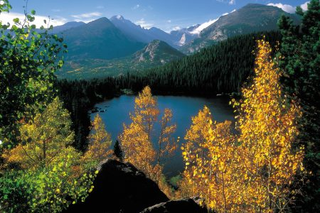 A view of a lake and the mountain range in Rocky Mountain National Park just as the leaves are starting to change color.
