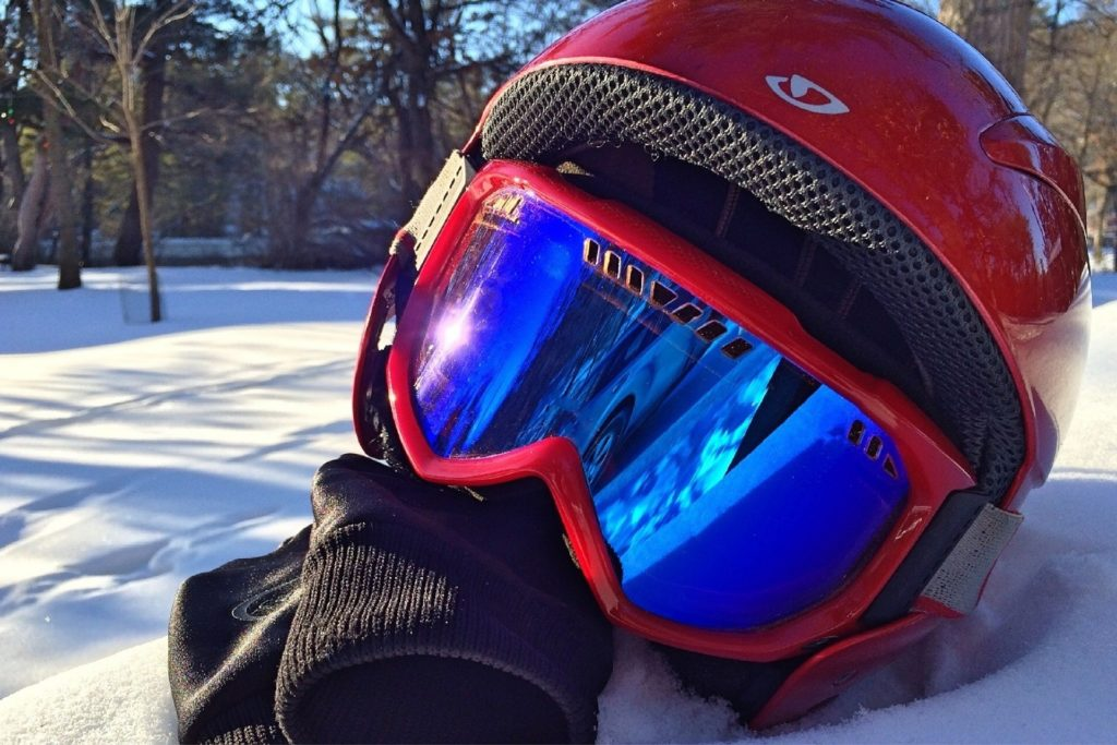 Packing essentials for your next snowboarding trip include helmet, goggles and gloves.