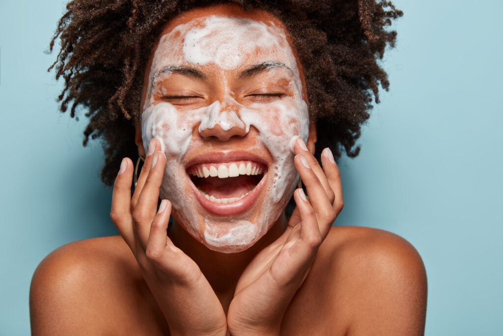 Portrait of beautiful woman with white foam mask on face, touches cheeks, enjoys softness of skin after beauty treatments.