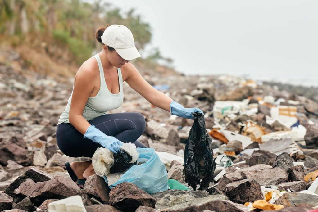Woman volunteer in gloves holds plastic garbage on the background of sea coast.