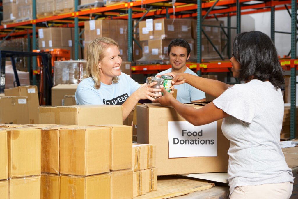 Volunteers Collecting Food Donations In Warehouse, another way to support hurricane relief.