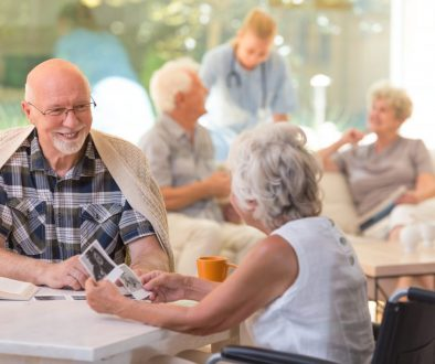 Married couple of elders sitting together and watching old photos at senior living community. Photo: Adobe Stock