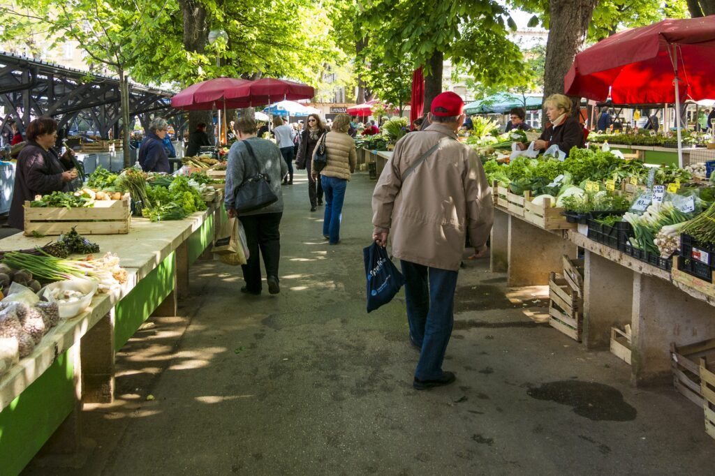 To travel like a local and save money, shop at farmer's markets and prepare meals at your vacation home rental.